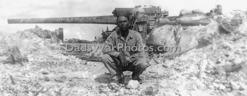 Ben Jones, a fellow soldier from Louisiana poses in front of a Japanese Type 10 120-mm dual purpose gun that has been disabled by U.S. infantry. This is one of the enemy guns that was firing on my father's battalion from on top of the ridge.
